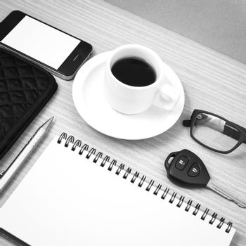 coffee and phone with notepad,car key,eyeglasses and wallet on wood table background black and white color