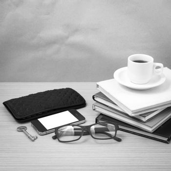 coffee and phone with stack of book,key,eyeglasses and wallet on wood background black and white color