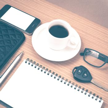 coffee and phone with notepad,car key,eyeglasses and wallet on wood table background vintage style
