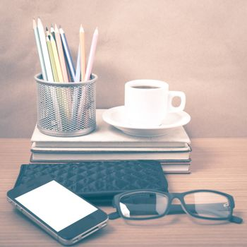 office desk : coffee with phone,stack of book,eyeglasses,wallet,color pencil box on wood background vintage style