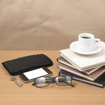 coffee and phone with stack of book,key,eyeglasses and wallet on wood background