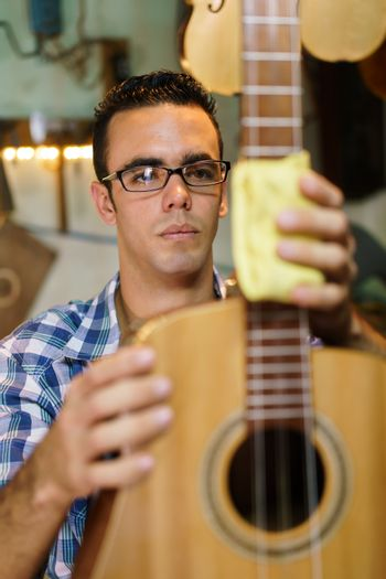 Lute maker shop and acoustic music instruments: young adult artisan focused on cleaning and wiping an old classic guitar. Medium Shot