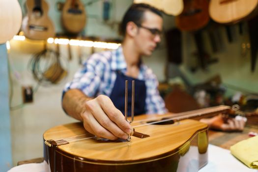 Lute maker shop and classic music instruments: young adult artisan fixing old classic guitar, tuning the instrument with a metallic diapason. Closeup of hand on guitar body