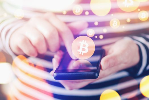 Woman paying with Bitcoins over mobile smartphone