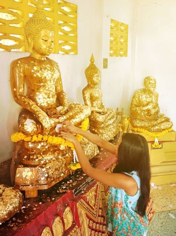 women putting the gold sheet on the buddha statue and praying for good luck in life