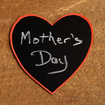 A heart with a mothers day announcement using a chalkboard.