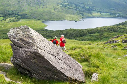 big rock with hikers on the kerry way in irelands wild atlantic way