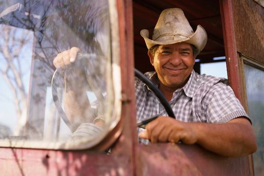 Farming and cultivations in Latin America. Portrait of middle aged hispanic farmer sitting proud in his tractor at sunset, holding the steering wheel. He looks at the camera and smiles happy.