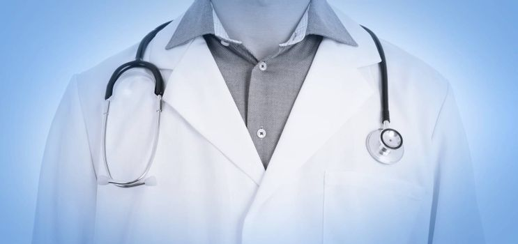 Close up of male doctor with stethoscope, isolated, medical blue
