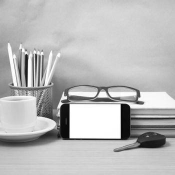 office desk : coffee and phone with car key,eyeglasses,stack of book,pencil box black and white color