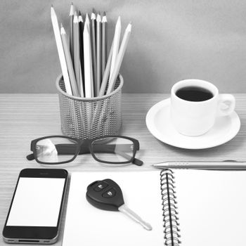 office desk : coffee and phone with key,eyeglasses,notepad,pencil boxblack and white color