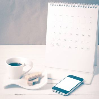 coffee cup with wafer,phone,calendar on white wood background vintage style