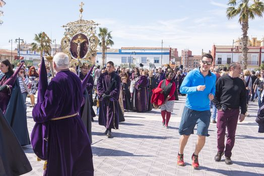 """SPAIN, Valencia: People run and take a walk as penitents of the """"Cristo Salvador y del Amparo"""" (Christ the Saviour and Protector) brotherhood walk by during the Good Friday procession on the paseo de Neptuno, in front of Malvarrosa beach, in Valencia, on March 25, 2016. Christian believers around the world mark the Holy Week of Easter in celebration of the crucifixion and resurrection of Jesus Christ."""