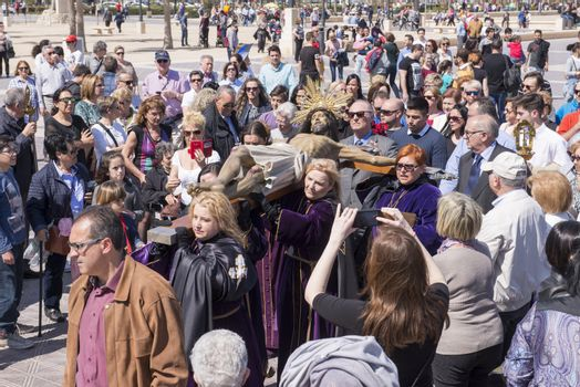 """SPAIN, Valencia: Onlookers watch and take pictures of penitents of the """"Cristo Salvador y del Amparo"""" (Christ the Saviour and Protector) brotherhood walking by during the Good Friday procession on the paseo de Neptuno, in front of Malvarrosa beach, in Valencia, on March 25, 2016. Christian believers around the world mark the Holy Week of Easter in celebration of the crucifixion and resurrection of Jesus Christ."""
