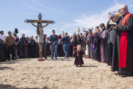 """SPAIN, Valencia: Penitents of the """"Cristo Salvador y del Amparo"""" (Christ the Saviour and Protector) brotherhood take part in the Good Friday celebration on Malvarrosa beach, in Valencia, on March 25, 2016. Christian believers around the world mark the Holy Week of Easter in celebration of the crucifixion and resurrection of Jesus Christ."""