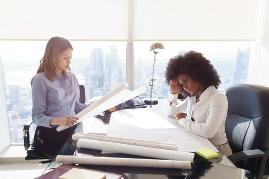 Team of two female architects, sitting at desk in office skyscraper. The women talk reviewing a building plan. Medium shot