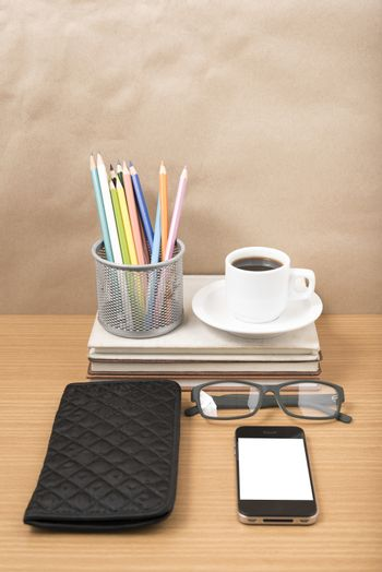 office desk : coffee with phone,stack of book,eyeglasses,wallet,color pencil box on wood background