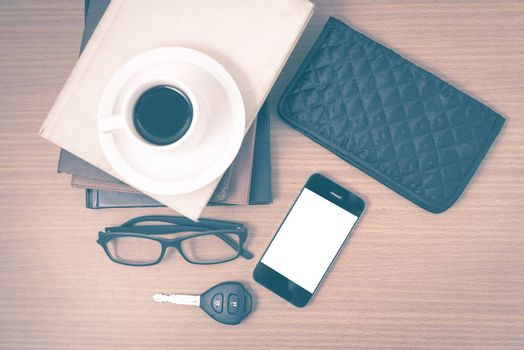 coffee and phone with stack of book,car key,eyeglasses and wallet on wood background vintage style