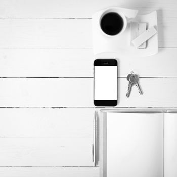 coffee cup with wafer,phone,key,notebook on white wood background black and white color