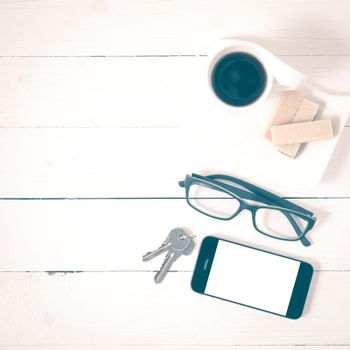 coffee cup with wafer,phone,key,eyeglasses on white wood background vintage style
