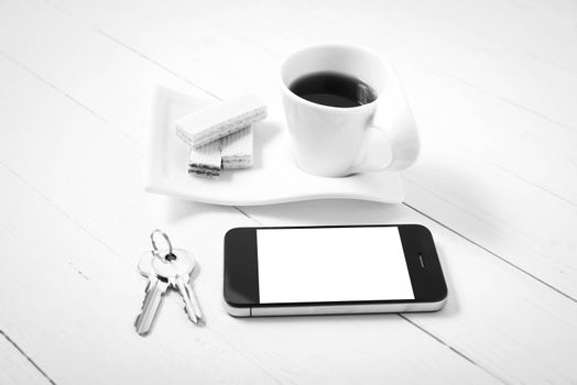 coffee cup with wafer,phone,key on white wood background black and white color