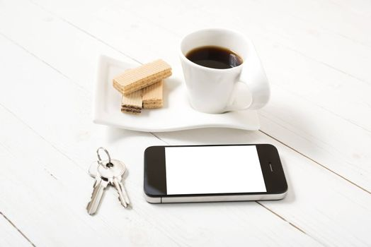 coffee cup with wafer,phone,key on white wood background