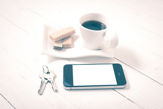 coffee cup with wafer,phone,key on white wood background vintage style