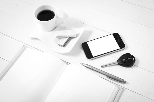 coffee cup with wafer,phone,car key,notebook on white wood background black and white color