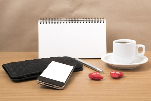 working table : coffee with phone,notepad,wallet and red heart on wood background