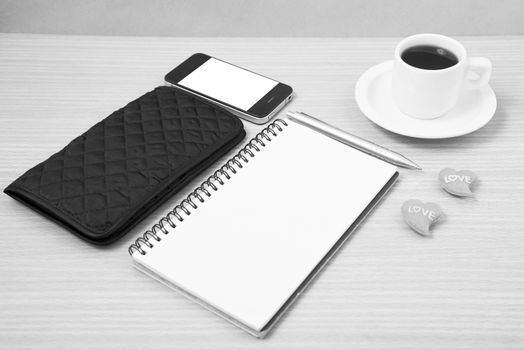 working table : coffee with phone,notepad,wallet and red heart on wood background black and white color