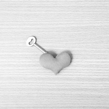 red heart with key on wood table background black and white color