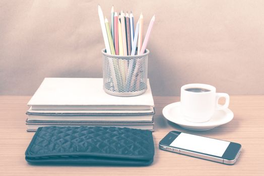office desk : coffee with phone,stack of book,wallet,color box on wood background vintage style