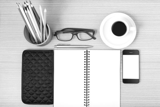 office desk : coffee with phone,notepad,eyeglasses,wallet,color pencil box on wood background black and white color