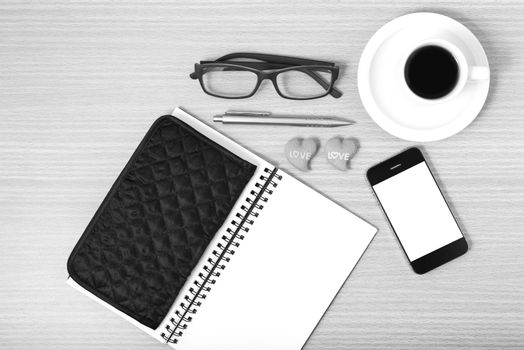 office desk : coffee with phone,notepad,eyeglasses,wallet,heart on wood background black and white color