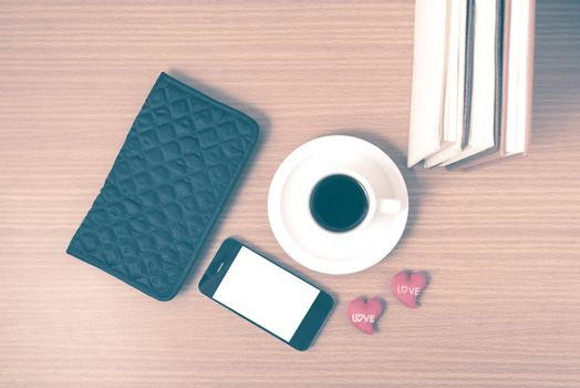 office desk : coffee with phone,heart,stack of book,wallet on wood background vintage style