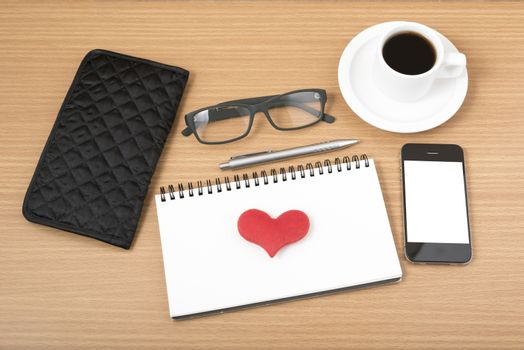 office desk : coffee with phone,notepad,eyeglasses,wallet,heart on wood background