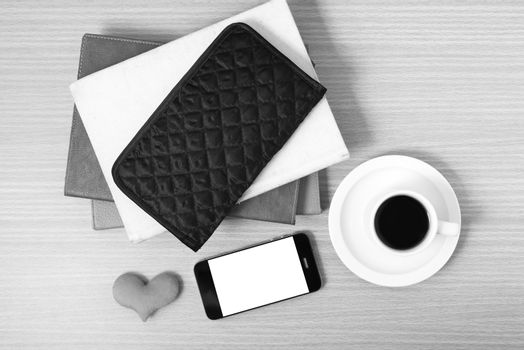working table : coffee with phone,stack of book,wallet and heart on wood background black and white color