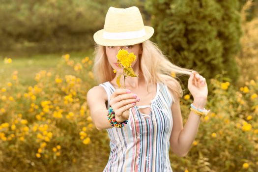 Beauty playful woman relax in summer garden smiling, people, outdoors, bokeh. Attractive happy blonde girl in hat with flower enjoying nature, harmony on meadow, lifestyle. Sunny day, forest,copyspace