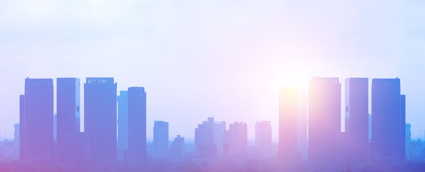 Silhouetted colorful office buildings with soft light from sunrise on the white sky