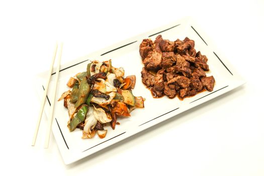 The Chinese fried beef in sweet-sour sauce and stewed vegetables. On a white background.