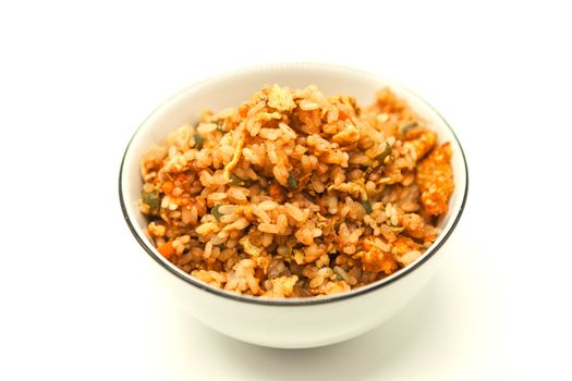 Fried Chinese rice with vegetables and egg, in a bowl on a white background. Chinese favourite garnish.