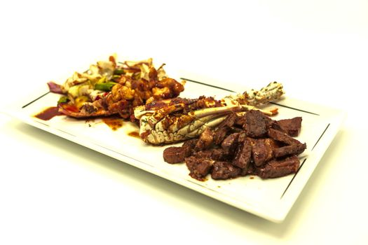 Surf and turf, fried lobster and juicy stake with a garnish from fried vegetables.