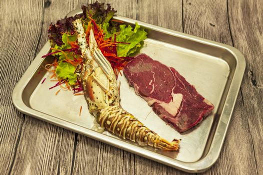 Set for surf and turf a fresh crude lobster and a juicy piece of a marble stake on a tray.