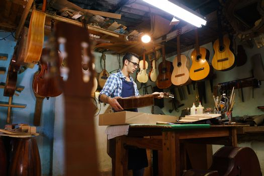 Lute maker shop and acoustic music instruments: a young adult artisan fixes an old classic guitar, then stores it in a cardboard case for his client. Wide shot
