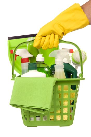 Vertical shot of a yellow gloved hand carrying a basket of green environmentally safe cleaning supplies.