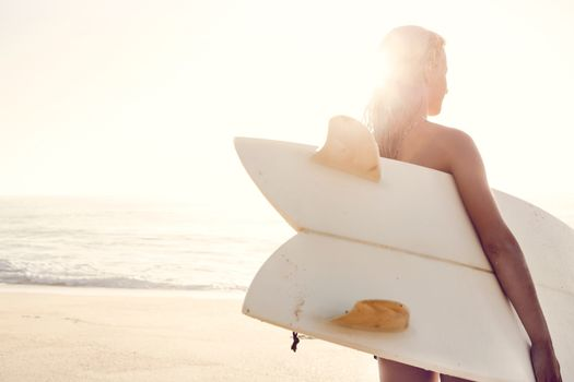 Beautiful young woman holding her surfboard after a day of surf