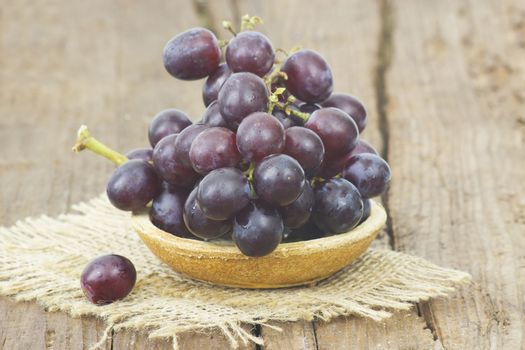 grapes in a bowl on wooden background