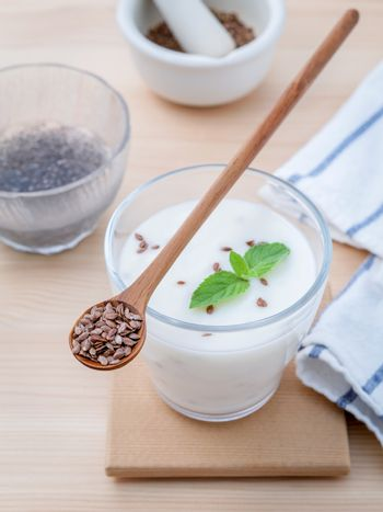 Nutritious flax seeds with glass of greek yogurt and wooden spoo