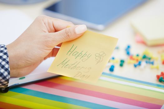 Human hand holding adhesive note with Happy mothers day text