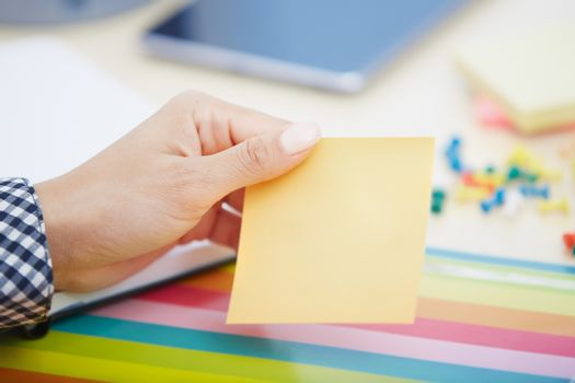 Human hand holding adhesive note with empty space
